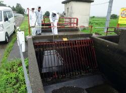 雨の中、水路のゴミ上げ作業